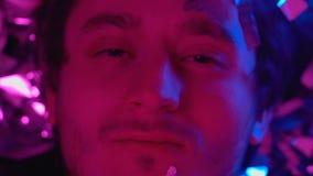 Uomo ubriaco che si trova fra i coriandoli e che esamina macchina fotografica, intossicazione dell'alcool archivi video
