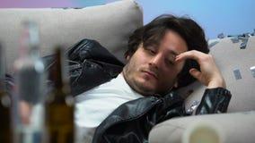 Uomo ubriaco che sveglia sul sofà nel posto sconosciuto dopo il partito, dipendenza di alcool stock footage