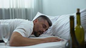 Uomo ubriaco con l'emicrania che sveglia dopo il partito di notte, disordine nella sala, postumi di una sbornia video d archivio