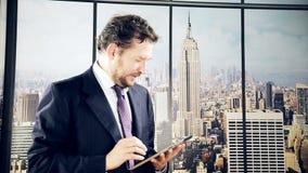 Uomo in ufficio che fa affare con la compressa a New York video d archivio
