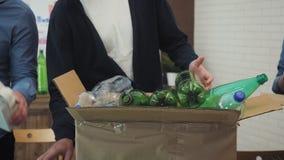 Uomo in ufficio che mette lo spreco della plastica nel recipiente di riciclaggio video d archivio