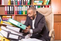 Uomo in ufficio con molto lavoro di ufficio annoiato fotografia stock libera da diritti