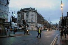 Uomo in un alto rivestimento di visibilità che attraversa la strada sul headrow nel centro urbano di Leeds alla penombra che guar fotografia stock