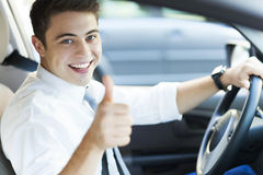 Uomo in un'automobile con i pollici su Immagini Stock Libere da Diritti