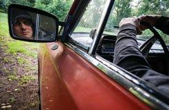 Uomo in un'automobile rossa fotografie stock