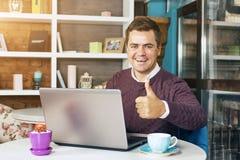 Uomo in un caffè con sorridere del computer portatile Fotografia Stock