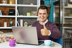 Uomo in un caffè con sorridere del computer portatile Fotografie Stock Libere da Diritti