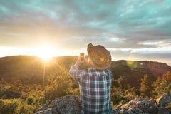 Uomo in un cappello che fa un selfi al tramonto Tipo che fa un selfi con uno smartphone fotografia stock