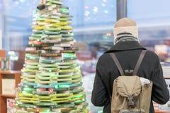 Uomo in un cappotto grigio in una libreria Fotografia Stock