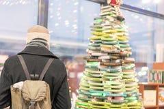 Uomo in un cappotto grigio in una libreria Il concetto di auto-istruzione fotografia stock libera da diritti