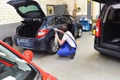 Uomo in un'officina che pulisce un servizio automobilistico per il cliente immagine stock