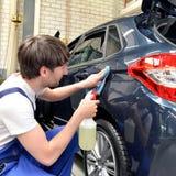 Uomo in un'officina che pulisce un servizio automobilistico per il cliente fotografia stock libera da diritti