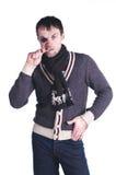 Uomo in un pullover che morde un chip Fotografia Stock Libera da Diritti