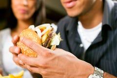 Uomo in un ristorante che mangia hamburger