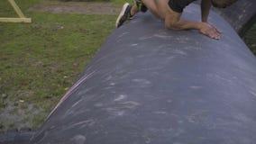 Uomo in un tamburo rampicante di corsa ad ostacoli video d archivio
