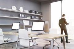Uomo in un ufficio con quattro monitor del computer Fotografia Stock Libera da Diritti