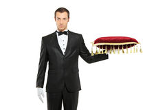 Uomo in un vestito nero che tiene un cuscino Immagini Stock