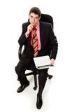 Uomo in un vestito, sedentesi in una presidenza, computer portatile. Fotografia Stock Libera da Diritti