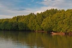 Uomo in una barca che galleggia sul fiume Fotografie Stock