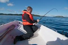 Uomo in una barca con la canna da pesca Immagine Stock
