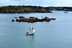 Uomo in una barca a vela di legno minuscola in porto Manech Brittany France Europe immagini stock