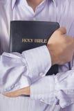 Uomo in una bibbia di abbraccio della camicia Fotografia Stock