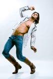 Uomo in una camicia bianca, in jeans ed in caricamenti del sistema Fotografie Stock