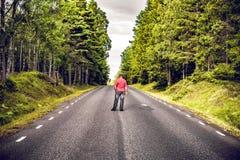 Uomo in una camicia rossa che guarda giù una strada asfaltata fotografia stock