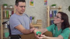Uomo in una clinica di riabilitazione che subisce riabilitazione dopo una lesione che tiene un estensore del polso stock footage