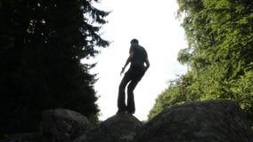 Uomo in una foresta che salta sulle rocce stock footage