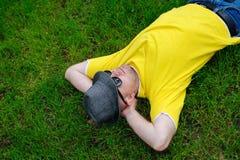 Uomo in una maglietta ed in un cappello gialli che si trovano sull'erba immagine stock libera da diritti