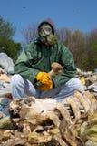 Uomo in una maschera antigas che si siede sull'immondizia e che tiene un osso Immagine Stock