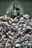 Uomo in una maschera antigas che si siede sull'immondizia e che tiene un osso Fotografie Stock
