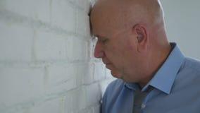 Uomo in una posizione disperata che tiene la sua testa sulla superficie della parete dentro l'ufficio R fotografie stock