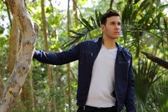 Uomo in una regolazione della natura con la mano sull'albero Fotografia Stock