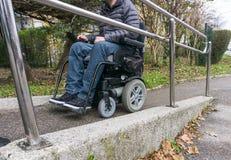 Uomo in una sedia a rotelle facendo uso di una rampa accanto alle scale fotografia stock