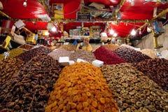 Uomo in una stalla dell'alimento che dà mestolo pieno dei dadi alla macchina fotografica circondata dai frutti e dai dadi colorat fotografie stock