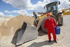 Uomo in uniforme di rosso con la latta della benzina, bulldozer nel fondo Fotografia Stock