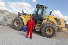 Uomo in uniforme di rosso con la latta della benzina, bulldozer nel fondo Immagine Stock