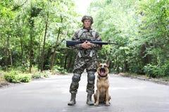 Uomo in uniforme militare con il cane da pastore tedesco immagini stock libere da diritti