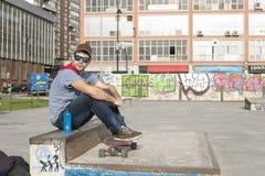 Uomo urbano con gli occhiali da sole blu ed il pattino che si siedono sul parco. Fotografia Stock Libera da Diritti