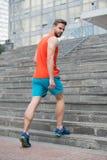Uomo in usura attiva e scarpe da tennis sui punti Allenamento dello sportivo sulle scale Misura e sicuro futuro e successo Aspett Fotografia Stock Libera da Diritti