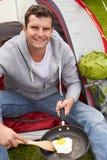 Uomo vacanza in campeggio che frigge uovo in pentola Fotografie Stock