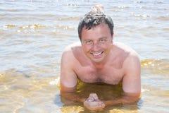 Uomo in vaction di estate che si trova sulle feste dell'acqua della sabbia fotografia stock libera da diritti