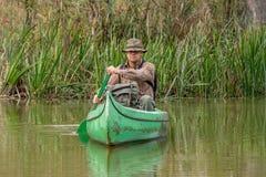 Uomo in vecchia canoa sul fiume immagini stock libere da diritti