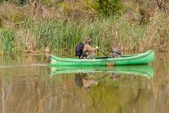 Uomo in vecchia canoa sul fiume con due zainhi e cappelli - paesaggio immagini stock