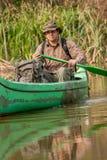 Uomo in vecchia canoa sul fiume con lo zaino ed il cappello fotografia stock libera da diritti