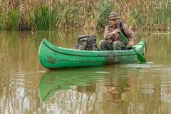 Uomo in vecchia canoa sul fiume con lo zaino - paesaggio fotografie stock libere da diritti