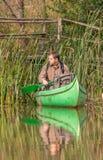 Uomo in vecchia canoa sul fiume davanti al vecchio ponte di legno immagine stock