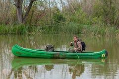 Uomo in vecchia canoa sul fiume - paesaggio fotografia stock libera da diritti